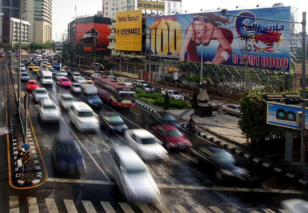 Pedestres se aproximam com cuidado de um cruzamento com carros em alta velocidade em Bancoc, na Tailândia (foto: Bernard Spragg/ Flickr)