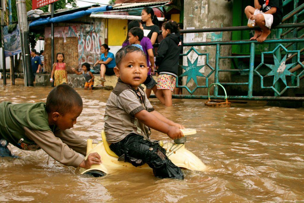 Crianças brincando durante enchente causada por fortes chuvas em Kampung Melayu, Jacarta. (Foto: Kate Lamb/Wikimedia Commons)